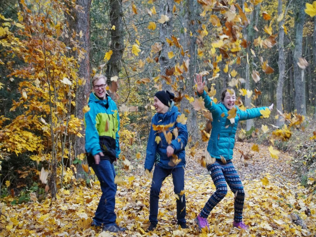 Three adolescent children playing in an autumn forest, as an example of what to do to prepare your children for moving.