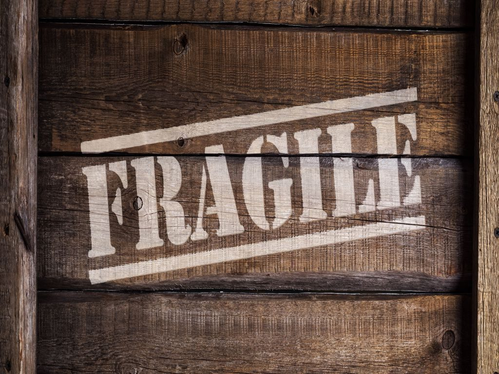 A wooden box with 'fragile' written with chalk.