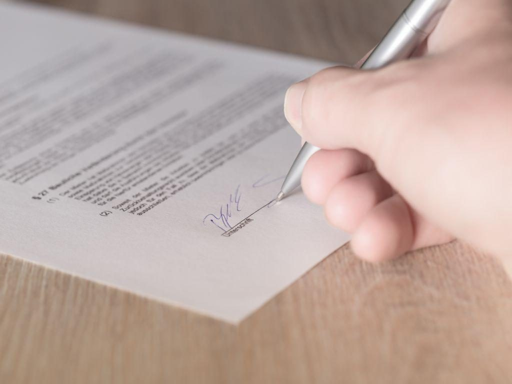 A person signing a moving contract.