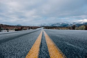 A country road covered with a thin sheet of ice and snow.