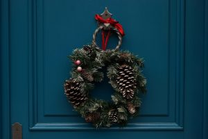 A wreath hanging on a blue door.