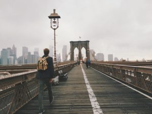 A person walking across the Brooklyn bridge. If you need someone who knows their way around New York - contact our movers East New York!