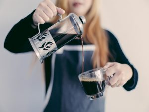 A woman pouring some coffee as a way to reward your movers.