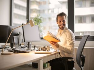 A man smiling while working in his office.