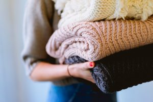 A woman holding three things of comfortable knitwear. Donate your stuff to the Red Cross or Goodwill.