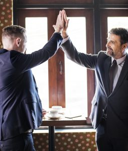 Two men high-fiving. They can get jobs because someone donated their stuff and they got good work suits.