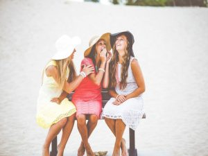 Three women in dresses with hats laughing, representing one of the biggest expat problems.