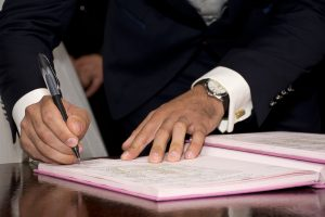 A white man writing something in a purple notebook. He's wearing a suit and watch. He's right handed. It's important not to sign what you haven't read, and to get everything in writing.
