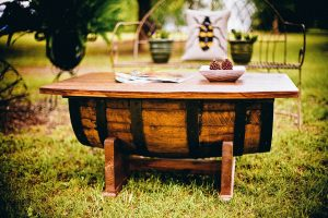 A charming wooden table in a grassy back yard. Pack your wooden furniture so you can use it for parties to come!