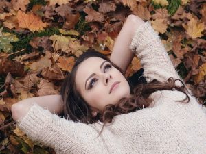 A woman laying in autumn leaves and thinking.