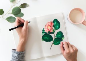 A person drawing a pink flower.