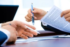 Two hands holding pens lifting papers