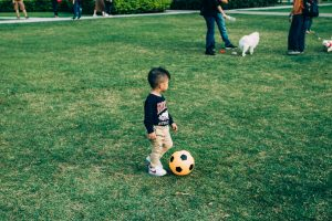 A four year old kicking a ball.