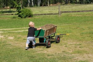 Young child playing on a ruined lawn.