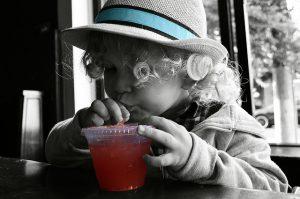 Child drinking red beverage.