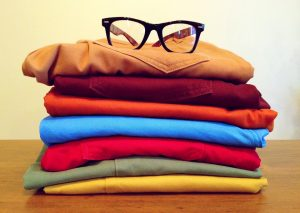 Pile of shirts and glasses on top.