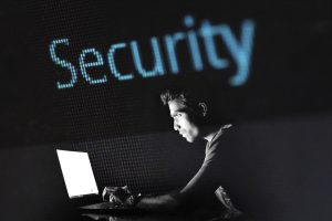 """Man typing on a laptop with word """"Security"""" above his head."""