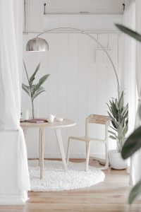 White room, washed wood furniture, silver lamp, pale green plants