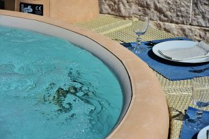 A Jacuzzi with bubbles and two champagne glasses next to it