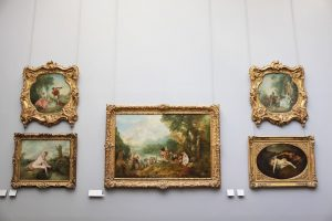 Five paintings in golden frames on a white wall