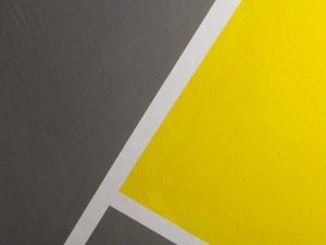 Gray, yellow and white geometric wall. Adding accent walls is one of the painting tips to transform your home.
