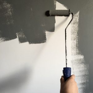 Person holding a paint roller and painting the wall gray