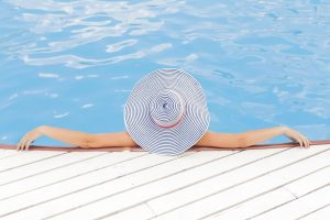 Woman in a hat sunbathing in the pool.