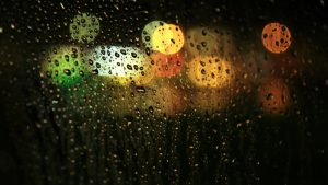 Night lights are seen through a window full of condensation