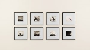 A white wall with eight pictures on it. One of the ideas for decorating your new home is making a gallery wall.