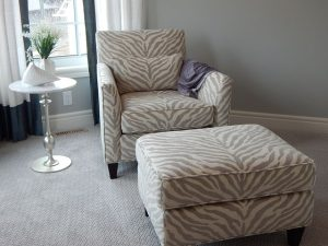 A chair and an ottoman with a pale zebra print