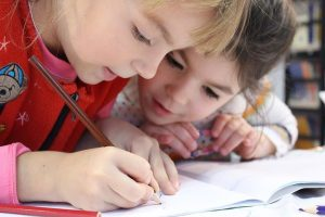 Kids writing down in notebooks