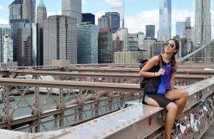 Girl sitting on the Brooklyn bridge thinking if Is raising your kids in Brooklyn a good idea