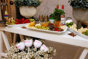 A table with wine bottles and glasses and fruits