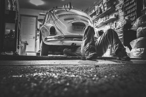 A black and white photo of a man working under a car before storing your vehicle ling-term
