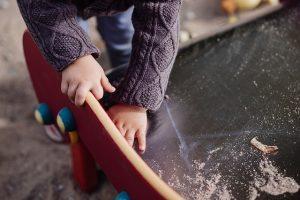 A child's hands climbing on a slide